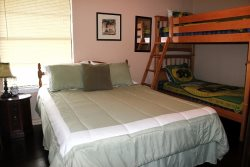 The 3rd bedroom has a full size bed and a set of bunk beds