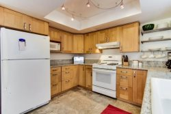 Newly remodeled kitchen with granite counters, beautiful cabnitry, new appliances and modern lighting