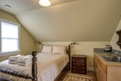 carriage house with queen bed, sink, kitchenette, electric teapot, bathroom, small TV, and internet access