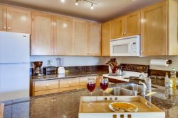 Remodeled California style open kitchen with breakfast bar, Alder wood custom cabinets and granite counter tops.