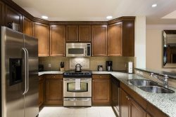 Spacious modern kitchen with granite counter tops and stainless steel appliances