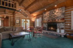 Living room with a river rock fireplace and vaulted ceilings