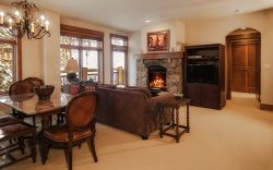 Upscale dining room table adjacent to the living room featuring a stone fireplace