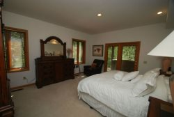 Cozy master bedroom with a king bed and French doors leading out to the patio