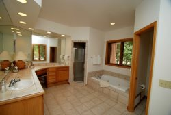 Spacious bathroom suite with large jetted tub, stand-up shower and dual sinks