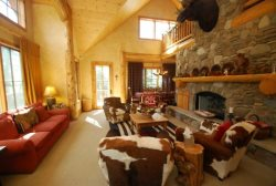 Massive river rock fireplace in the middle of the living room with cow hide furnishings