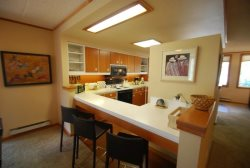 Full kitchen with a breakfast bar seating three guests