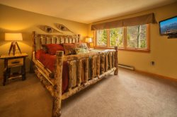Beautifully crafted log bed for a mountain style master bedroom