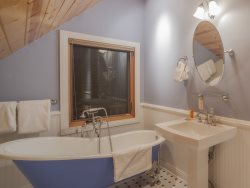 Deluxe master bathroom with a glass walk in shower, deep soaking tub, and dual sinks