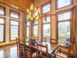 Dining areas by the ceiling high stone fireplace seating up to ten guests