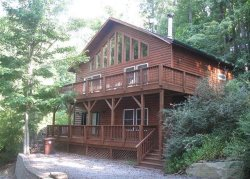 Two Story Log Cabin That Features A Wood Burning Fireplace And All New Furniture