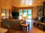 Living room with Woodstove, TV and view of Back Deck