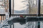 Image snow covered mountain views from a lakefront hot tub