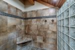 Walk in shower with stone tile and glass blocks.