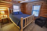 Main level bedroom with queen bed and attached bathroom.