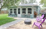 Beautiful well maintained back yard has a fire pit and chairs, BBQ grill