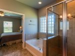 The master bathroom has a walk in tiled shower and huge tub