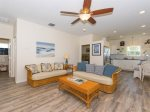 The living room has hardwood floors, a flat screen TV, and coastal decor