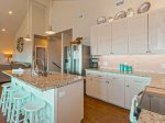 The kitchen is fully equipped with stainless steel appliances, microwave, and dishwasher