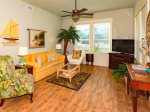 Open floor plan living room with tropical decor and wood flooring