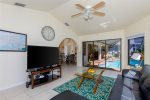 The family with big screen TV has great views to the pool area and a large couch