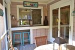 Bar area in screened in porch with two stools