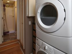 Guest house supplies second refrigerator and stackable washer and dryer for laundry.