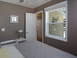 Master bedroom with a queen size bed and bench.  Additional dresser storage in the back breezeway room
