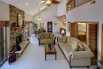 Great vaulted open floor plan living room with fireplace and dining area beyond.