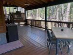 East Side of Wraparound Deck with Dining Table, TV, Gas Grill and Steps to Forest