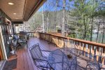Large back deck with gas grill and walkway to boathouse deck