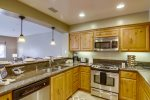 Stocked kitchen with stainless-steel appliances and granite counters