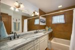 Hall bath with dual sink vanities and tub/shower combo