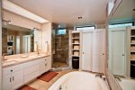 En suite bath with dual vanities, travertine tiling, walk in shower and soaking tub.