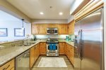 Open kitchen with granite counters and stainless appliances