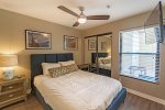 Main level bedroom 1 with queen bed, flat screen TV and ceiling fan