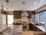 Gourmet kitchen with slab granite countertops and hardwood cabinetry