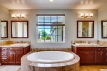 The elegant Master Bathroom features dual vanity sinks and a oval soaking tub