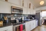 The well-equipped kitchen features granite counters and stainless appliances