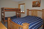 Eagle Trail Lodge bedroom with queen bed and bunk beds.