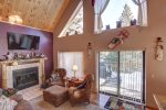 Knotty Pine Chalet living room with vaulted ceiling and wood burning fire place.