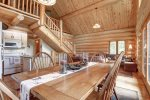 Dakota log Cabin dining room with vaulted ceilings and log stairs.