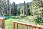 Black Bear Lodge deck view of forest and trout stream.