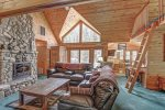 Black Bear Lodge living room with leather furniture and wood fireplace.