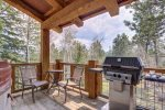 Iron Horse Cabin deck with gas grill and forest views.