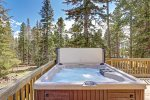 Front deck with hot tub and  patio table.