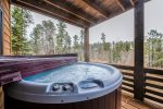 Camp Lodge Gold deck with hot tub and forest views.