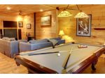 POOL TABLE IN BASEMENT AND SEATING AREA WITH BIG SCREEN TV