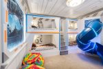 A fun kids room featuring custom built bunk beds with a slide