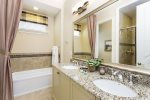 Ensuite bathroom with dual sink, walkin shower, and tub
